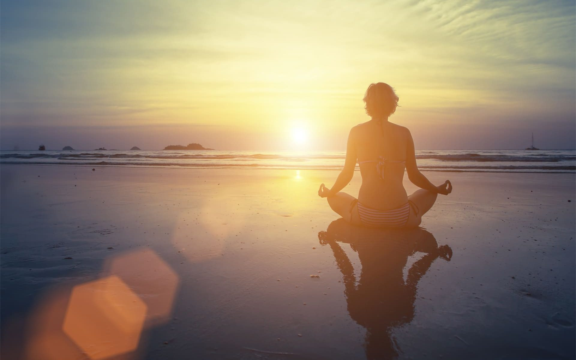woman sitting looking at sunset in yoga pose